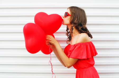 Pretty woman in red dress kissing air balloons heart shape over white background, profile view