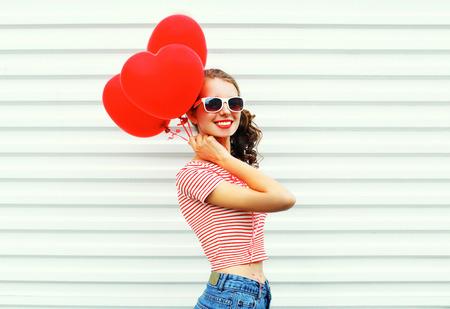 cola mujer: Feliz sonriente mujer con globos de aire corazón forma divertirse sobre fondo blanco Foto de archivo