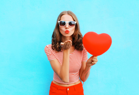 Portrait pretty woman sends air kiss with red balloon heart shape over blue background Stok Fotoğraf