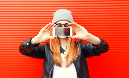 Fashion cool girl taking picture on smartphone self portrait, screen view, over red background