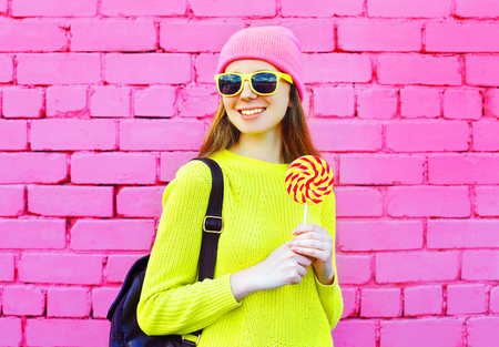 sweettooth: Fashion portrait smiling girl with lollipop over colorful pink brick background Stock Photo