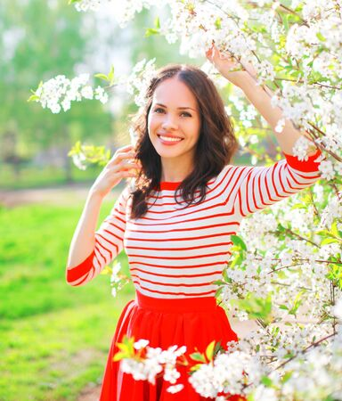 Portrait happy smiling young woman with spring flowers at garden Stock Photo