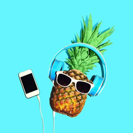 Fashion pineapple sunglasses and headphones listens to music on smartphone over blue background