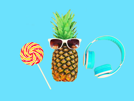 sweettooth: Fashion pineapple with sunglasses lollipop caramel and headphones over colorful blue background