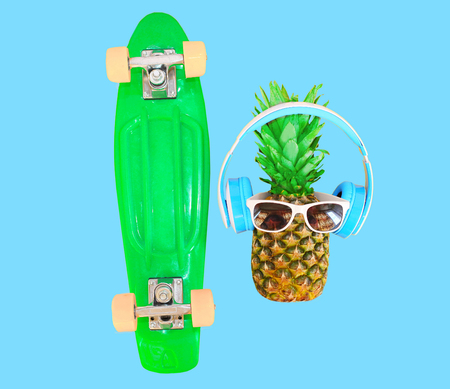 Pineapple with headphones sunglasses and skateboard over colorful blue background