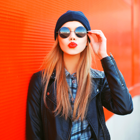Fashion portrait beautiful blonde woman sends air kiss blowing red lips outdoors wearing sunglasses and hat Banco de Imagens
