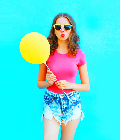 Fashion portrait woman wearing a t-shirt, denim shorts with yellow air balloon over colorful blue background