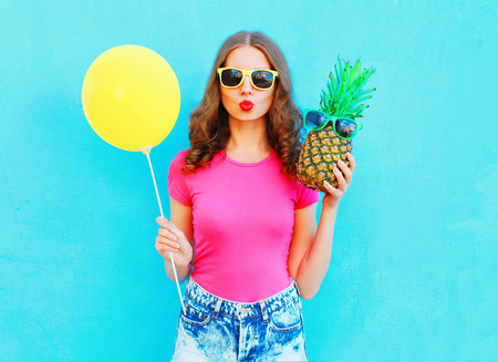 Fashion pretty woman with yellow air balloon and pineapple wearing a pink t-shirt over colorful blue background