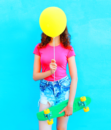 Fashion woman hiding face yellow air balloon with skateboard having fun over colorful blue background