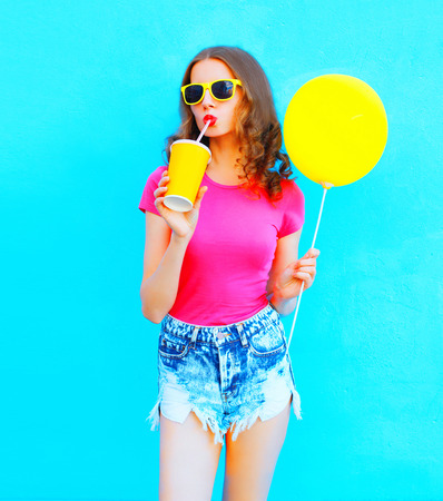 Fashion young woman wearing a t-shirt, denim shorts drinks fruit juice from cup with yellow air balloon over colorful blue background Stok Fotoğraf
