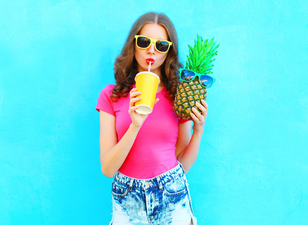 Fashion portrait pretty cool girl and pineapple drinking juice from cup over colorful background