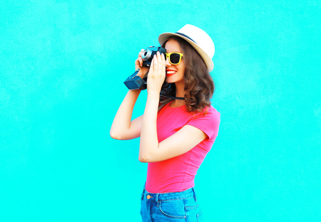 Fashion pretty woman taking picture wearing straw summer hat, sunglasses and vintage camera over colorful blue background Stock Photo