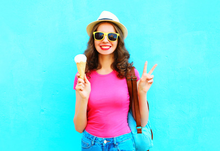 Fashion smiling young woman with ice cream over wearing straw hat colorful blue background Stok Fotoğraf