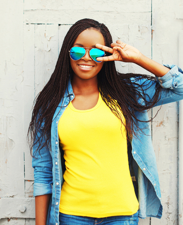 rastas: Fashion portrait pretty smiling young african woman in a sunglasses is having fun at city