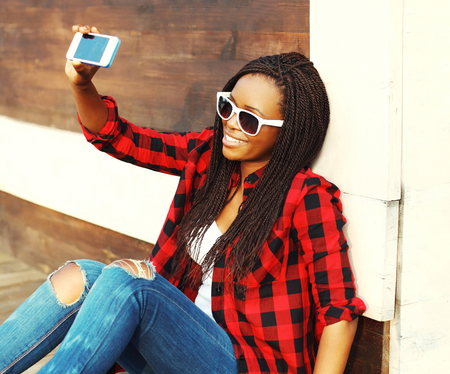Fashion pretty smiling african woman is taking picture self portrait on smartphone having fun in the city Stock Photo