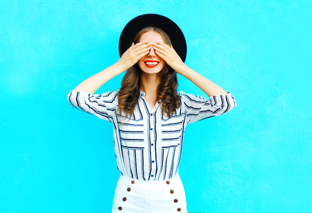 Fashion young smiling woman is closes hides her eyes having fun over colorful blue background