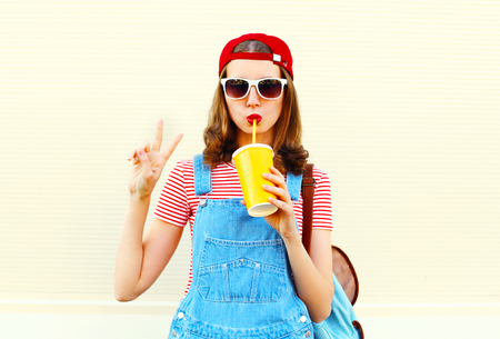Fashion pretty cool girl is drinks a juice from cup over white background
