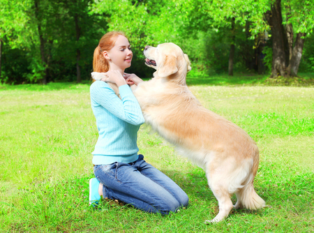 paw smart: Happy owner woman is training her Golden Retriever dog on the grass in a summer park