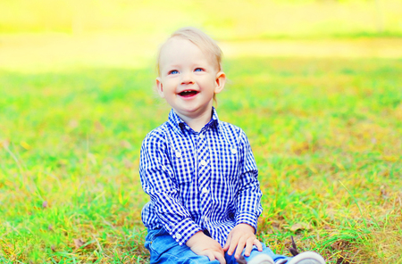 Happy smiling little boy child is sitting on the grass in a sunny day Stock Photo