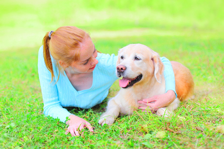 Happy smiling owner woman and Golden Retriever dog is lying on the grass Stock Photo