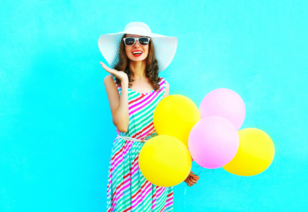Fashion happy smiling woman with an air colorful balloons is having fun on a blue background wearing a straw summer hat