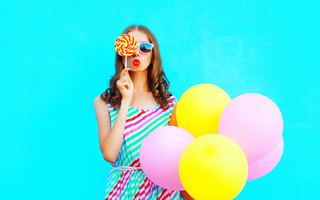 Fashion portrait pretty young woman with an air balloons, lollipop candy on a colorful blue background