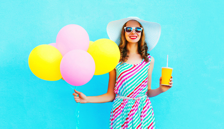 Fashion pretty smiling woman holds a fruit juice cup with an air colorful balloons over a blue background
