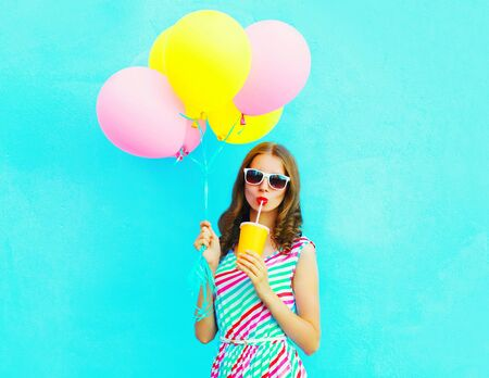Fashion pretty woman drinks fruit juice from cup holds an air colorful balloons on a blue background