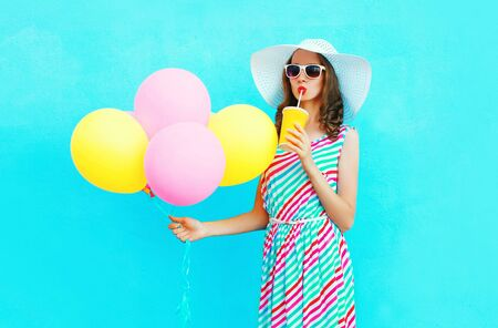 Fashion pretty woman drinks fruit juice from cup holds an air colorful balloons over a blue background Stock Photo