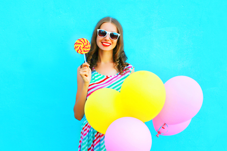 Fashion pretty young smiling woman with yellow an air balloons, lollipop candy on a colorful blue background