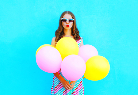 Fashion woman blowing lips making kiss an air colorful balloons on a blue background Stock Photo