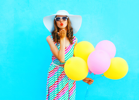 Fashion woman is sends an air kiss holds an air colorful balloons on a blue background wearing a straw summer hat and dress
