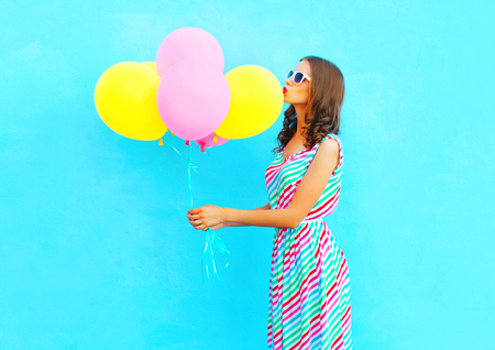 Fashion woman kissing an air colorful balloons on a blue background