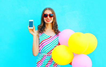 Happy smiling woman shows smartphone holding an air colorful balloons on a blue background