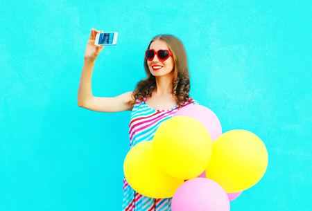 Happy smiling woman taking a picture on a smartphone with an air colorful balloons on a blue background