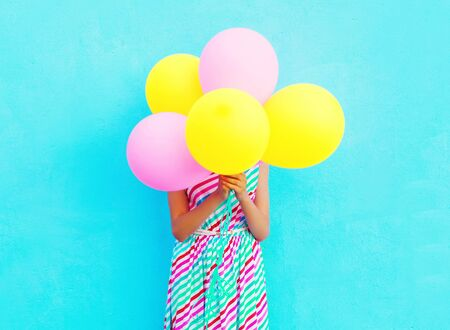 Happy woman is hides her head an air colorful balloons having fun over a blue background