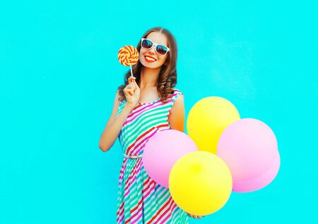 Pretty young smiling woman with an air balloons, lollipop candy on a colorful blue background Stock Photo