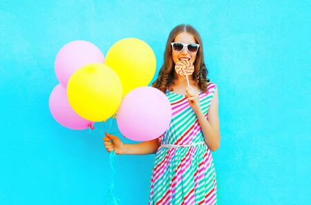 Pretty young woman with an air balloons bites a lollipop candy over a colorful blue background