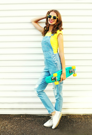 Fashion smiling woman holds a skateboard posing over a white background