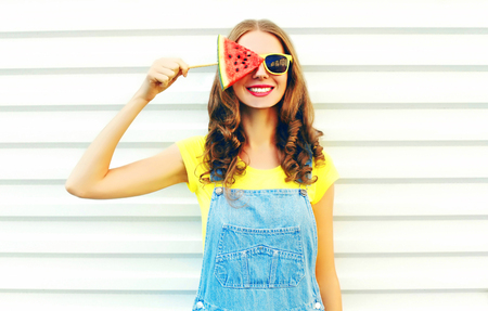 Fashion smiling young woman holding a slice of watermelon in the form of ice cream over a white background Stock Photo