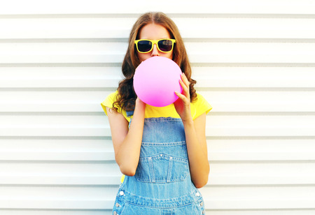 Fashion woman blowing a pink air balloon on a white background