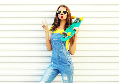 Fashion young woman blowing her lips with a skateboard over a white background