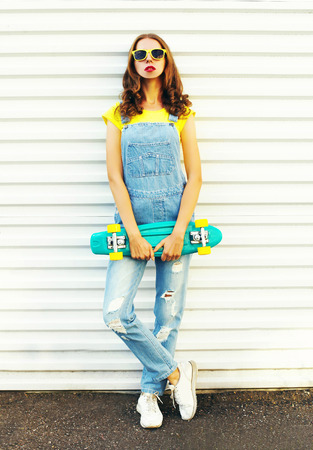 Fashion young woman with a skateboard on a white background