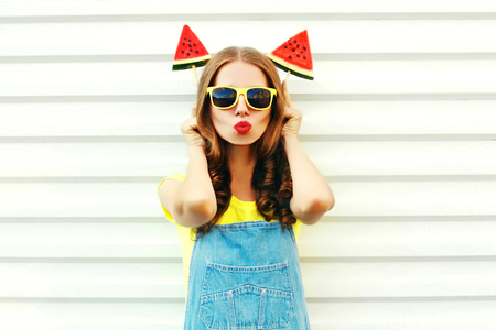 Funny pretty cool girl with a watermelon ice cream blowing her lips over a white background
