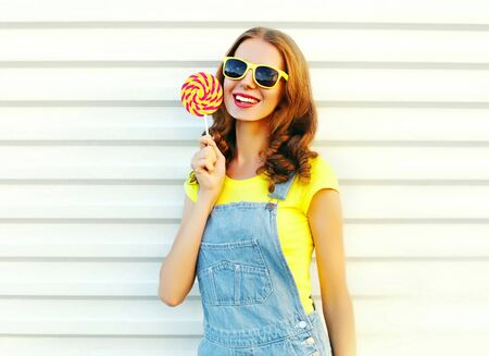 Happy smiling girl with a lollipop on the stick over a white background