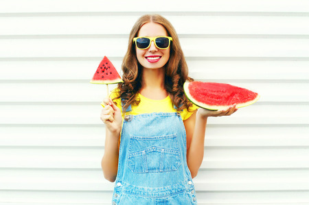 smiling young woman with a slice of watermelon in the form of ice cream on a white background