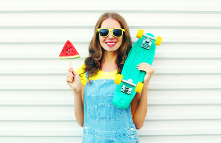 Fashion cheerful smiling woman with a slice of watermelon ice cream skateboard on a white Stock Photo