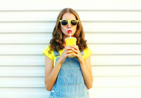 Fashion portrait pretty cool girl drinks a juice from cup over a white background Stock Photo
