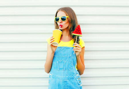 Fashion portrait pretty cool girl drinks juice from cup with slice watermelon ice cream