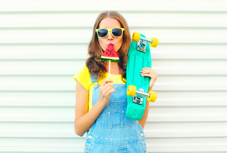 Fashion pretty cool girl eating a slice of watermelon ice cream holds a skateboard on a white  Stock Photo